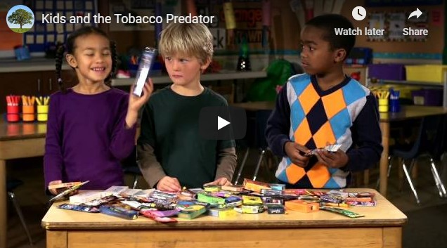 Three children stand behind a table with colorful tobacco products spread on it
