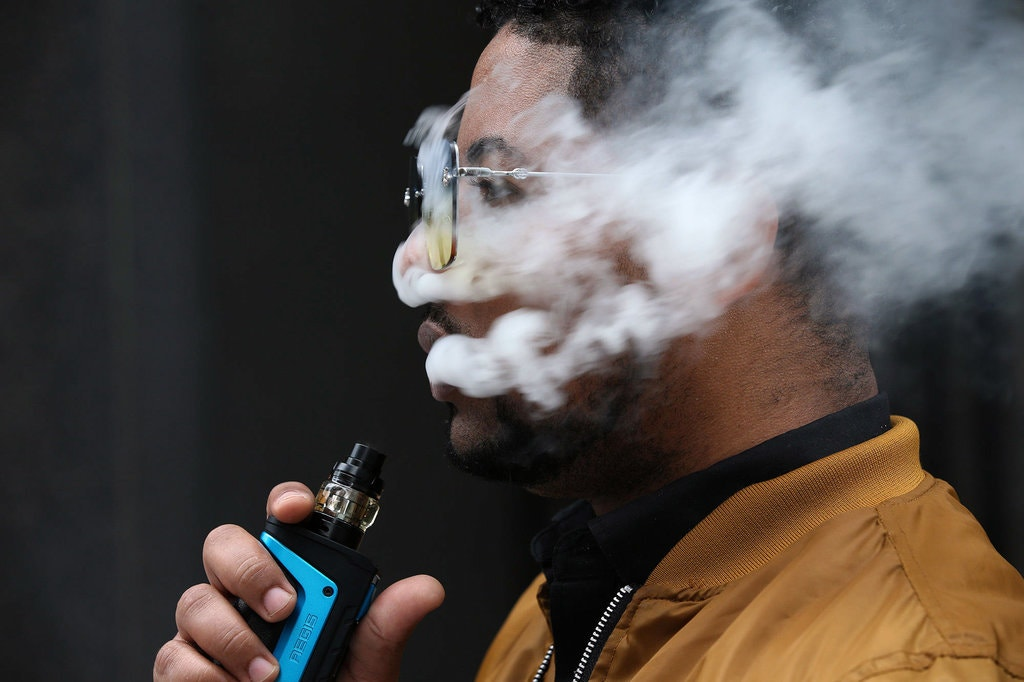 Man vaping, face covered with aerosol, holding blue mod e-cigarette
