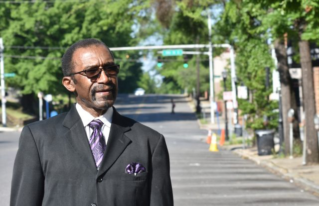 African American pastor standing in a neighborhood street