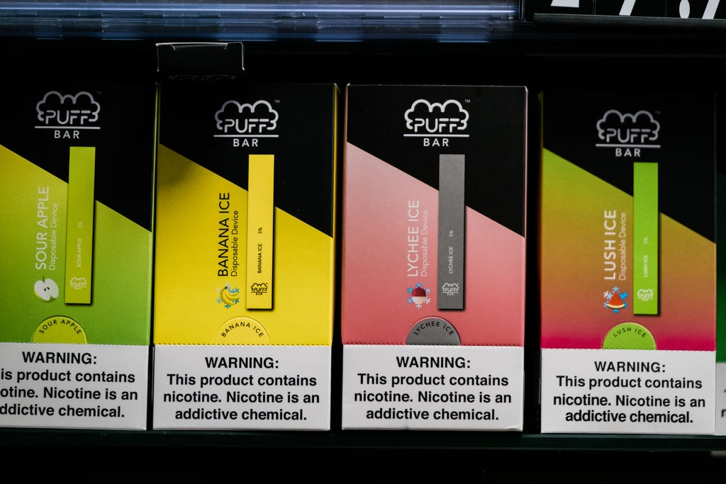 Four Puff Bar products in a retail display each is a different flavor: sour apple, banana ice, lychee ice, lush ice