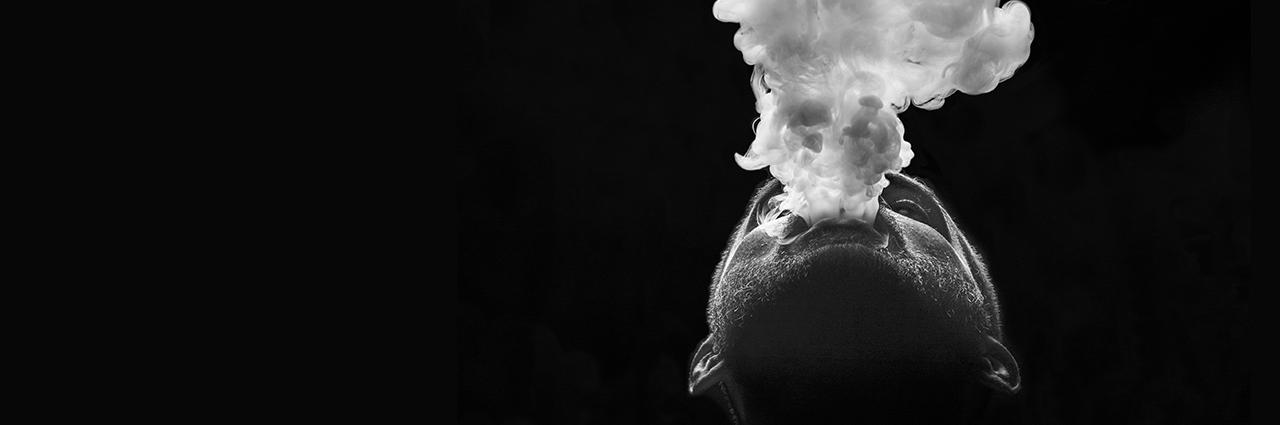 Man exhaling smoke while facing upwards